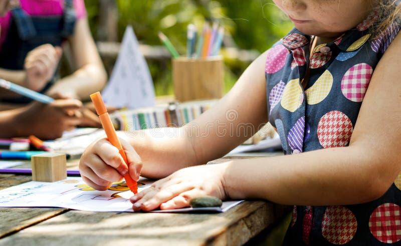 Groep de vrienden die van kleuterschooljonge geitjes kunstklasse in openlucht trekken stock foto