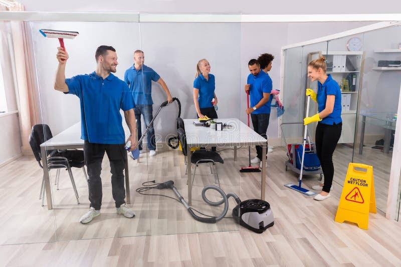 Groep Deskundige Portiers die Bureau schoonmaken stock afbeelding