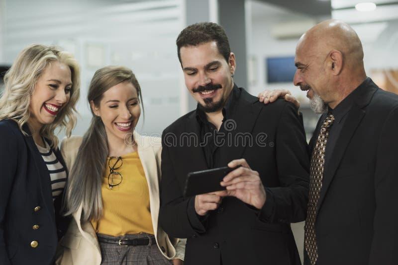 Groep die arbeider telefoon in een baanonderbreking kijken stock foto