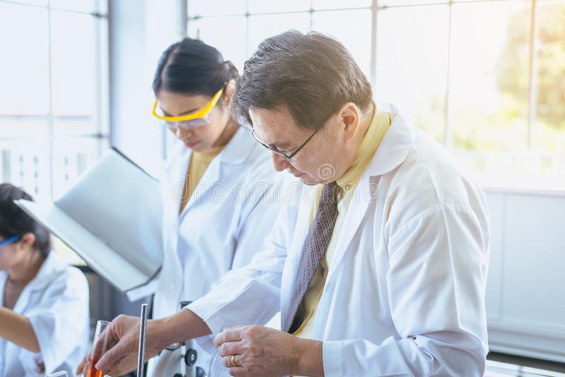 Groep die Aziatische wetenschapper en onderzoekinformatie in laboratary samenwerken verklaren stock foto