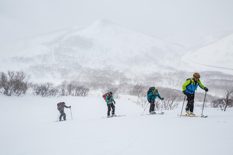 Groep die bergop in sneeuwstorm in backcountry van Hokkaido, Japan ski?en stock foto