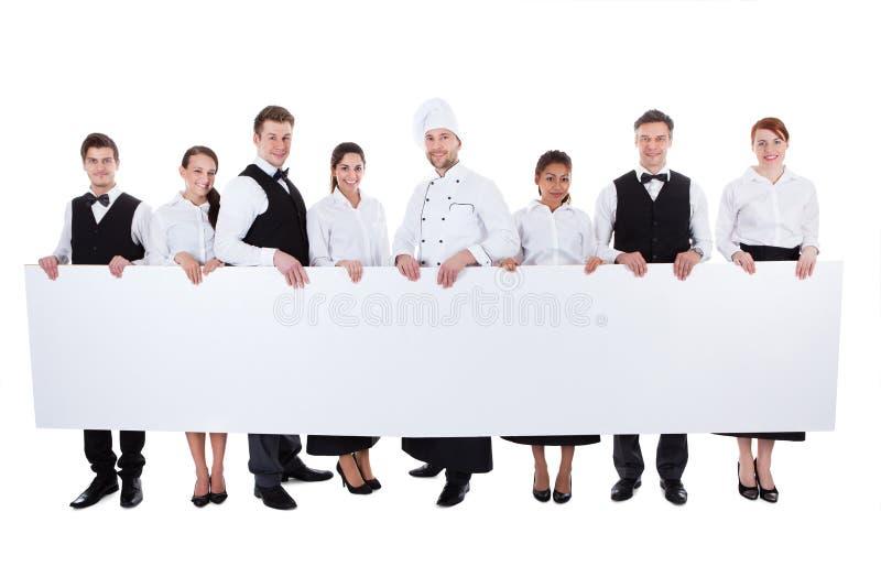Groep die cateringspersoneel een lege banner houden