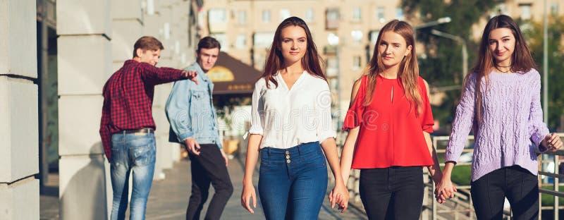 Groep die de jonge mens met vrouw in stad flirten stock fotografie