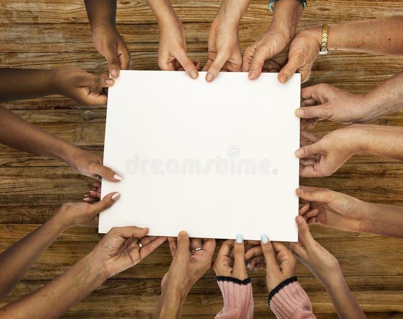 Groep die diversiteitshanden leeg document houden stock afbeelding