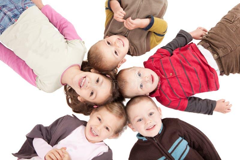 Groep die gelukkige jonge geitjes op ruggen op vloer ligt stock afbeeldingen