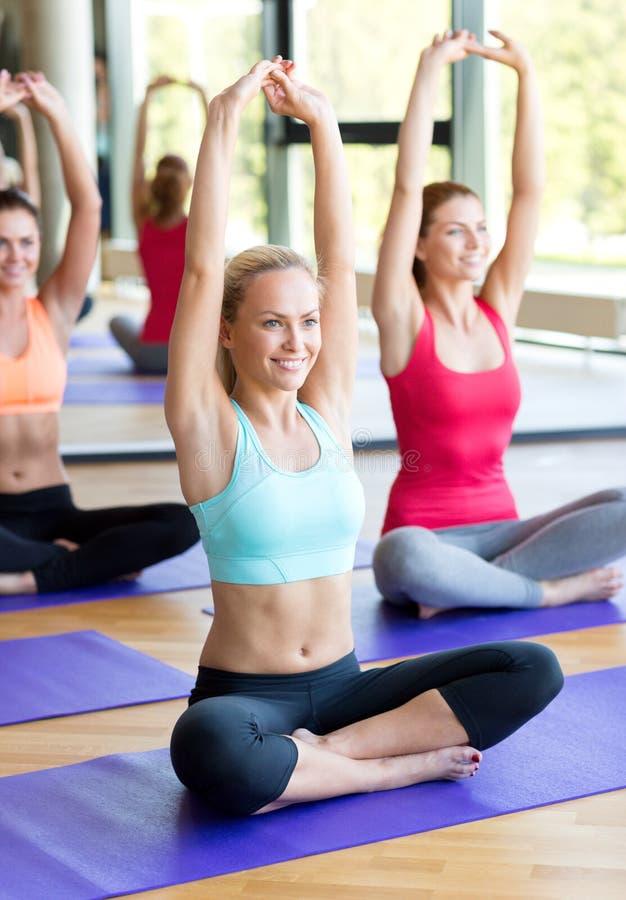 Groep die glimlachende vrouwen zich in gymnastiek uitrekken stock afbeeldingen
