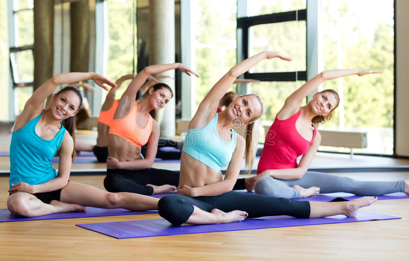 Groep die glimlachende vrouwen zich in gymnastiek uitrekken stock fotografie