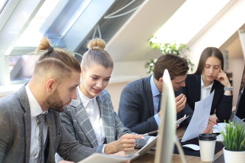 Groep die jonge bedrijfsmensen die, terwijl het zitten bij het bureau samen met collega's communiceren werken stock foto's
