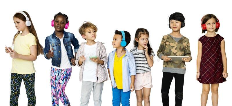 Groep die Jonge geitjes Digitale Apparaten het Luisteren Muziek op Witte Bla gebruiken stock afbeelding