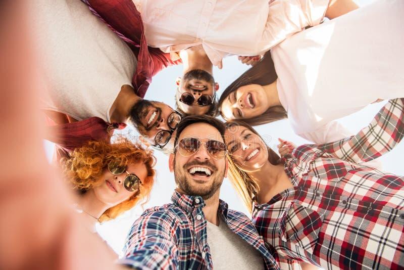 Groep die jongeren die zich in een cirkel bevinden, een selfie maken royalty-vrije stock afbeeldingen
