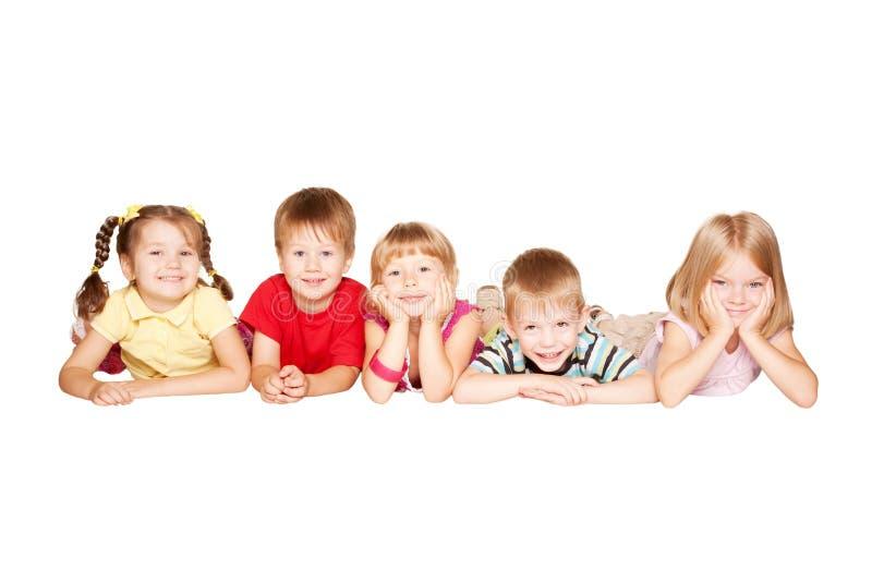 Groep die kinderen die pret hebben, op de vloer liggen stock foto's