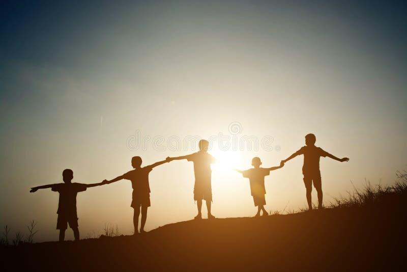 Groep die kinderensilhouetten handen samen houden stock foto