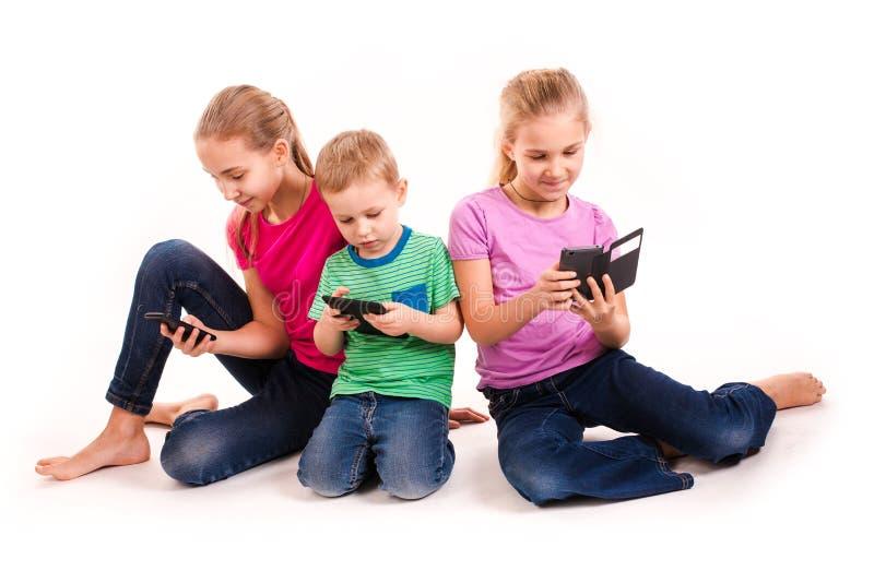 Groep die kleine jonge geitjes elektronische apparaten met behulp van stock afbeelding