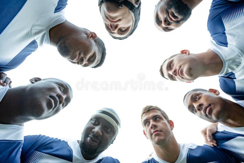Groep die Mannelijke rugbyspelers huddles zich in stadion vormen stock foto's