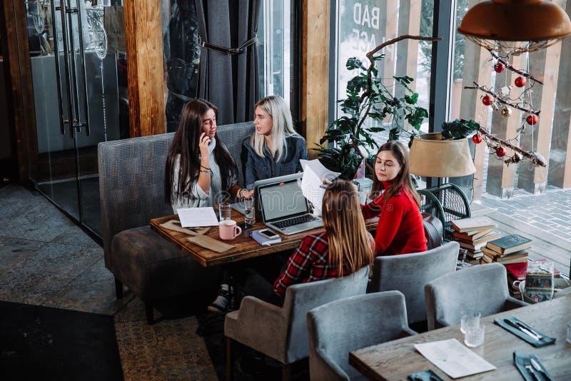 Groep die mensen aan bedrijfsproject bij koffie werken, bij lijst met bladen van document en laptop zitten royalty-vrije stock afbeeldingen