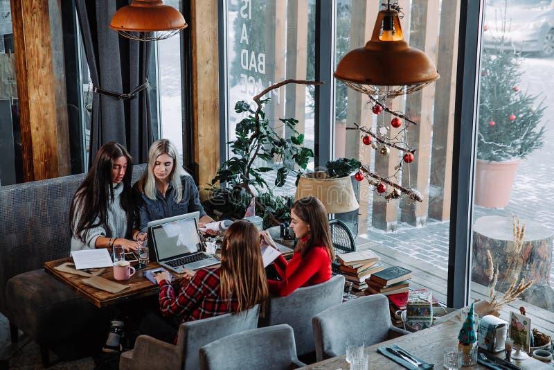 Groep die mensen aan bedrijfsproject bij koffie werken, bij lijst met bladen van document en laptop zitten stock fotografie