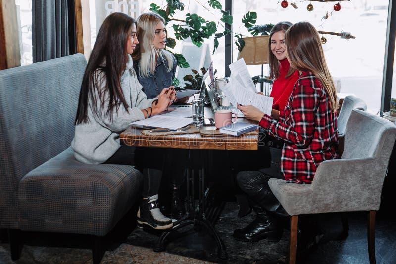 Groep die mensen aan bedrijfsproject bij koffie werken, bij lijst met bladen van document en laptop zitten royalty-vrije stock foto's