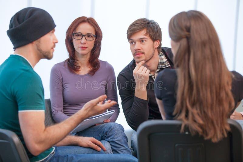 Groep die mensen aan welke jonge mens het zeggen luisteren. royalty-vrije stock foto