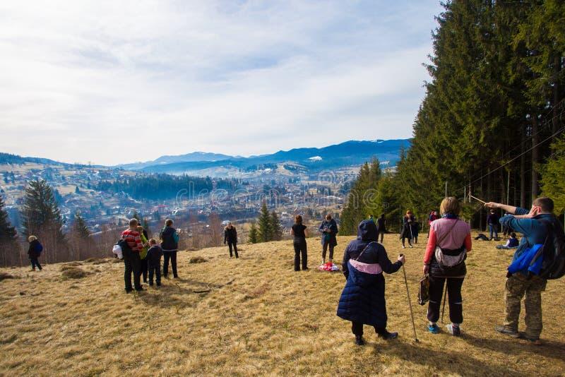 Groep die mensen in bergen in vroege de lente het bewonderen mening wandelen stock fotografie