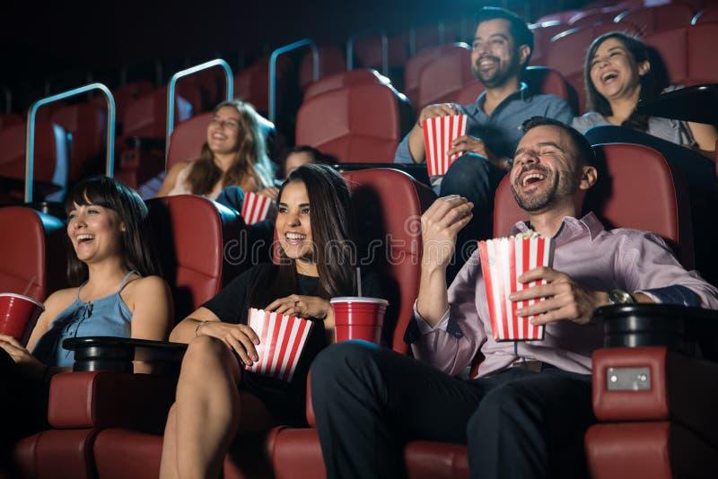 Groep die mensen bij de bioscoop lachen royalty-vrije stock fotografie