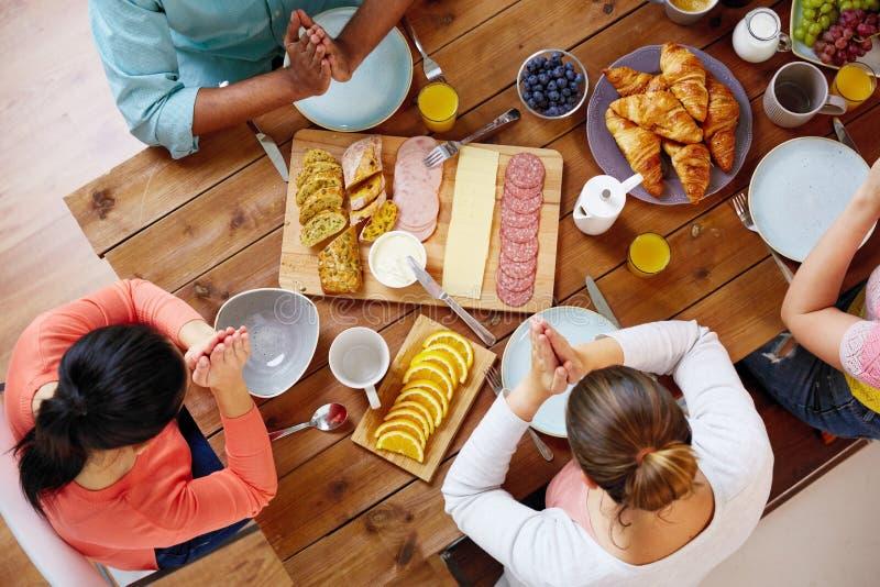 Groep die mensen bij lijst vóór maaltijd bidden royalty-vrije stock afbeelding