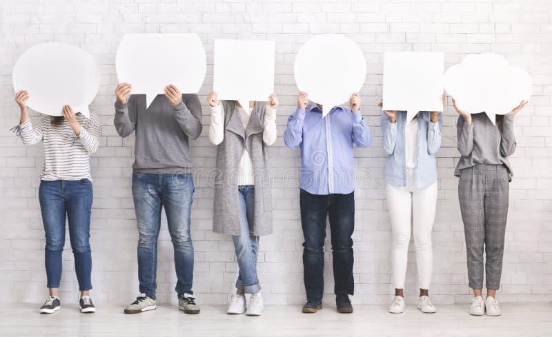Groep die mensen gezichten achter lege toespraakbellen verbergen stock foto's