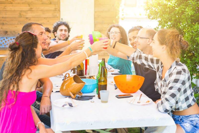 Groep die mensen hebbend lunch samen en roosterend zitten royalty-vrije stock foto