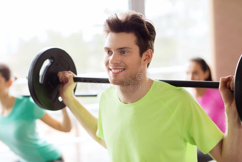 Groep die mensen met barbell in gymnastiek uitoefenen stock afbeeldingen