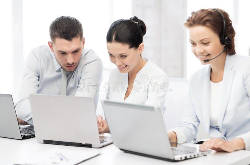 Groep die mensen met laptops in bureau werken stock afbeelding