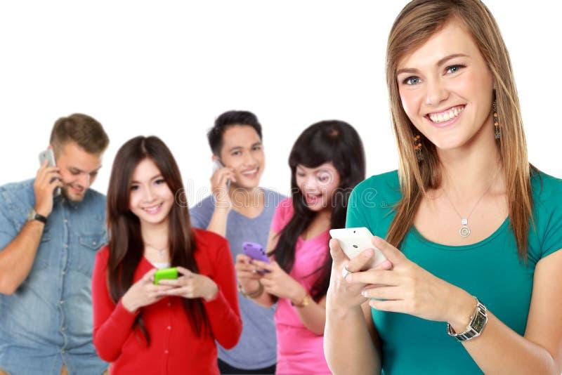 Groep die mensen mobiele telefoon met behulp van aantrekkelijke vrouw bij fron stock foto's