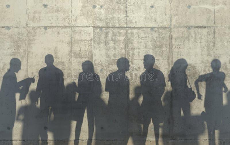 Groep die mensen in ontspannen de lopen stelt gegoten een schaduw op de concrete muur Conceptuele creatieve illustratie met silho stock fotografie