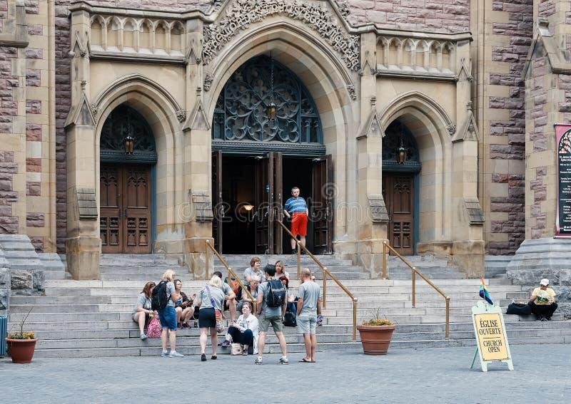 Groep die mensen op de ingangsladders zitten van St James United Protestant kerk stock foto's