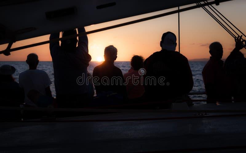 Groep die Mensen op de Zonsondergang letten stock foto's