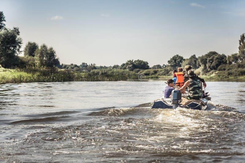 Groep die mensen op motorboot door rivier in de zomerdag aan het de jachtkamp tijdens jachtseizoen varen stock afbeeldingen