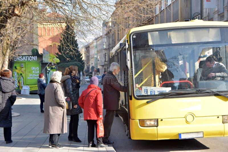 Groep die mensen in rij wachten om lokale stadsbus op bushaltepost in te gaan stock afbeeldingen