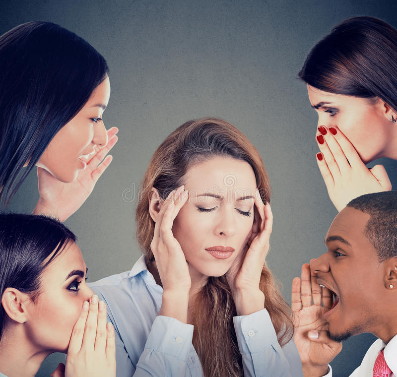 Groep die mensen roddel fluisteren aan een beklemtoonde vrouw die aan hoofdpijn lijden stock foto's