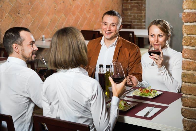 Groep die mensen uit merrily in het restaurant van het land dineren stock foto