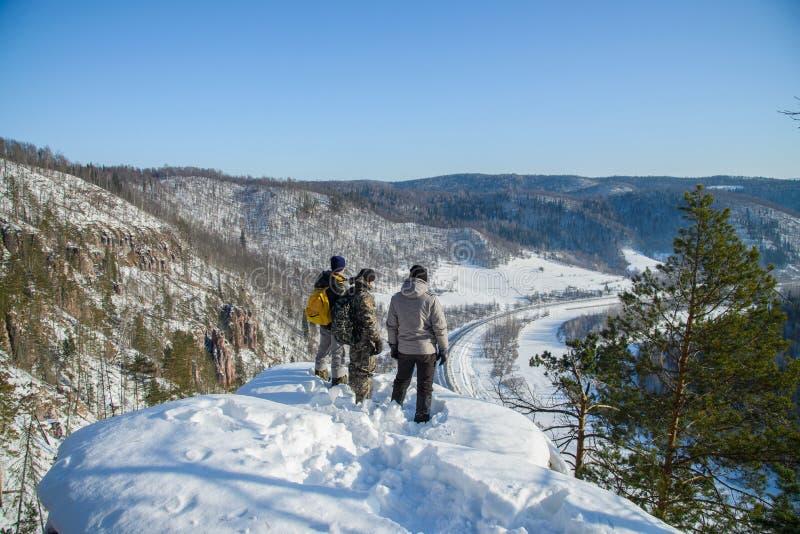 Groep die mensen zich bij bergpiek bij zonnige de winterdag bevinden royalty-vrije stock foto