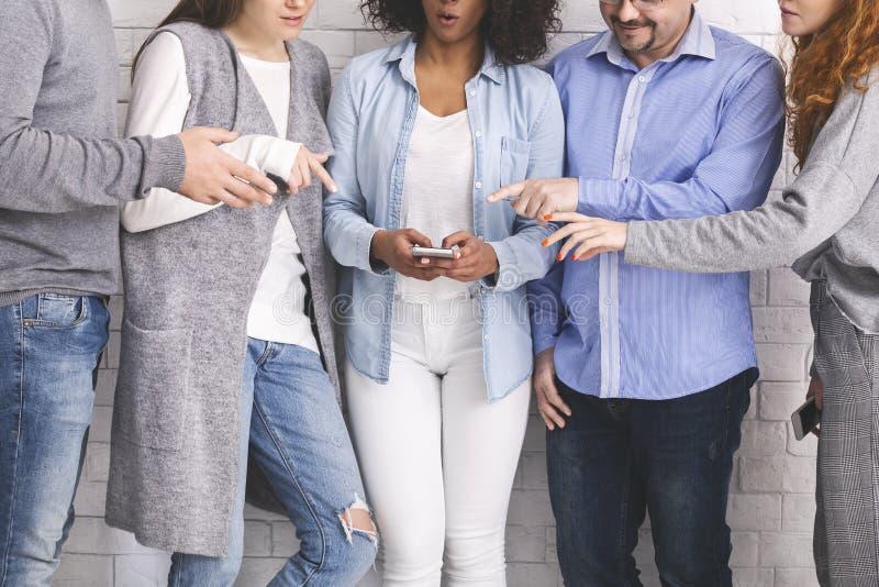 Groep die millennials handen bereiken aan cellphone stock fotografie