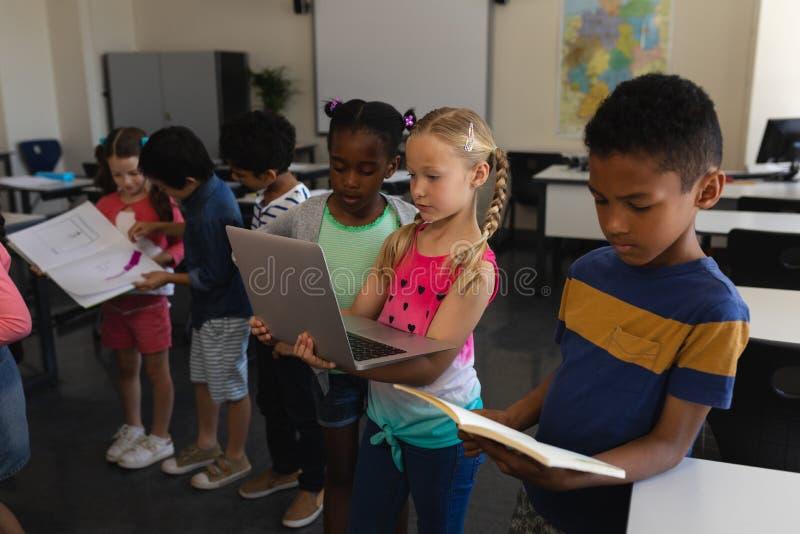 Groep die schooljonge geitjes samen in klaslokaal van basisschool bestuderen stock fotografie