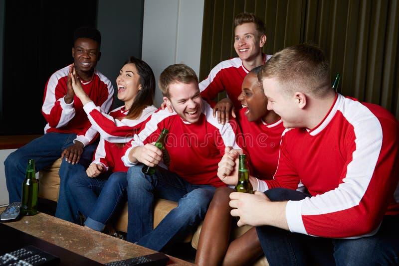 Groep die Sportenventilators op Spel op TV thuis letten royalty-vrije stock afbeeldingen