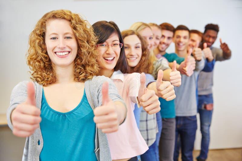Groep die tiener met omhoog duimen gelukwensen stock foto's