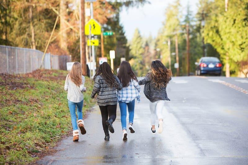 Groep die van vier jonge geitjes aan school lopen stock afbeeldingen