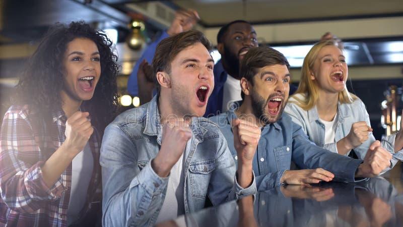 Groep die ventilators sport van spel genieten, uiterst gelukkig over winst, die in bar ontspannen royalty-vrije stock afbeelding