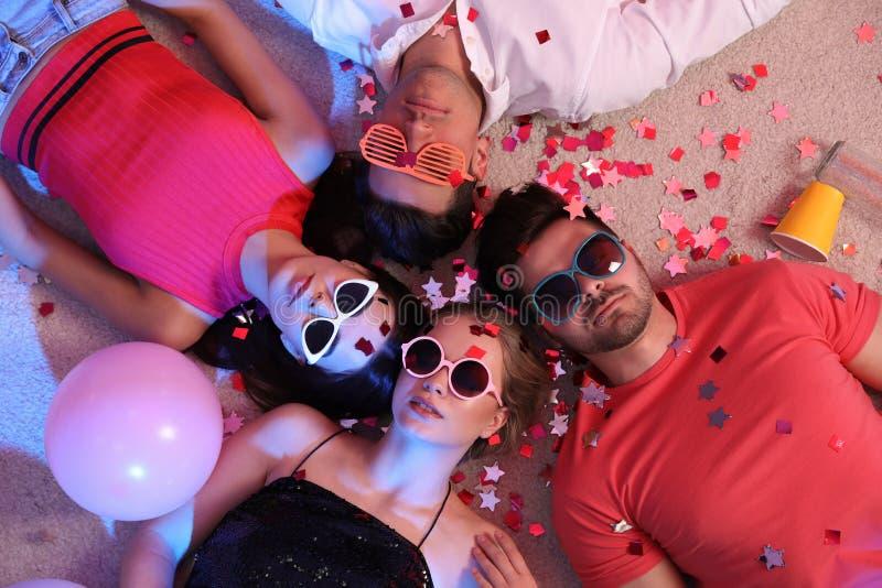 Groep die vrienden op slordige vloer na partij liggen royalty-vrije stock foto