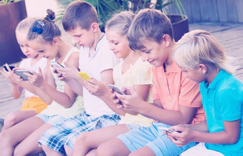 Groep die vriendschappelijke jonge geitjes met mobiele telefoons in openlucht spelen stock fotografie