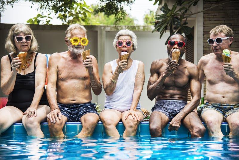 Groep diverse hogere volwassenen die roomijs samen eten stock afbeelding
