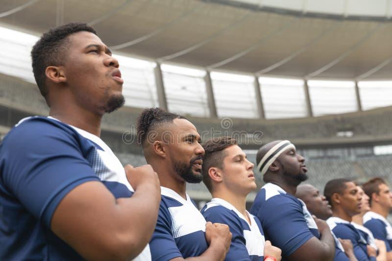 Groep diverse mannelijke rugbyspelers die belofte samen in stadion nemen royalty-vrije stock foto's