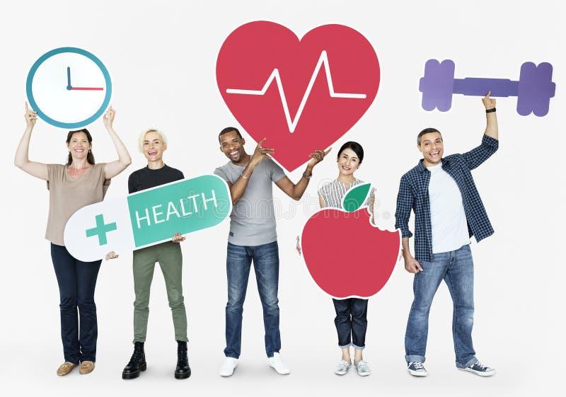 Groep diverse mensen die gezondheid en geschiktheidspictogrammen houden stock afbeeldingen