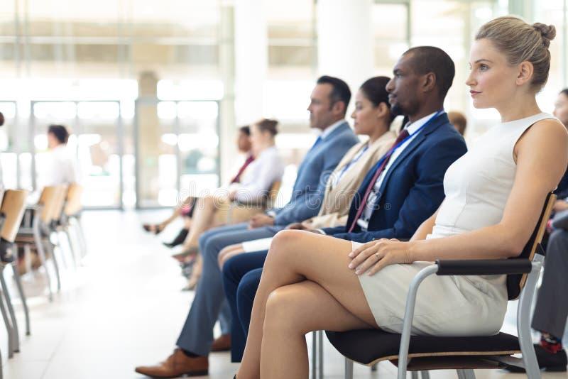Groep diverse stafmedewerkers die in conferentieruimte worden gezeten, die vooruit recht kijken stock afbeeldingen